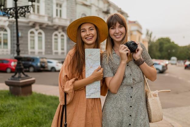 Стильные молодые женщины, путешествующие вместе по европе, одеты в модные весенние платья и аксессуары