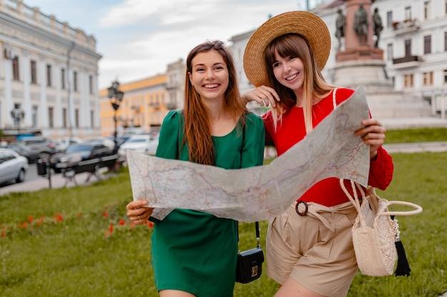 Стильные молодые женщины, путешествующие вместе по европе, одеты в модную весеннюю одежду и аксессуары