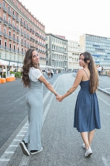 Stylish young women walking on street holding each other's hand