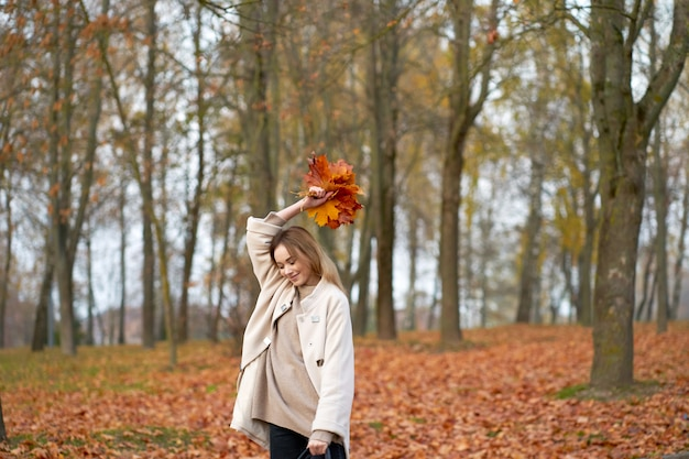 Stylish youth autumn collection. cheerful pretty girl wearing sweater, black jeans, trendy autumn coat holding  bouquet of autumn maple leaves.