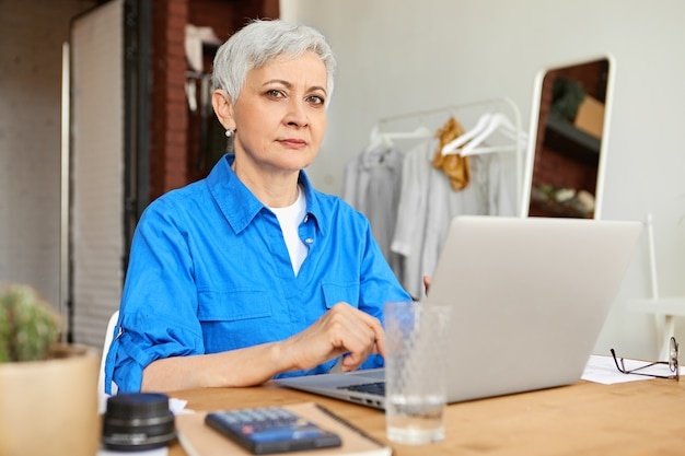 Stylishgray haired female photographer in her sixties sitting at home office in front of open laptop computer, uploading pictures. mature woman surfing internet using generic electronic gadget