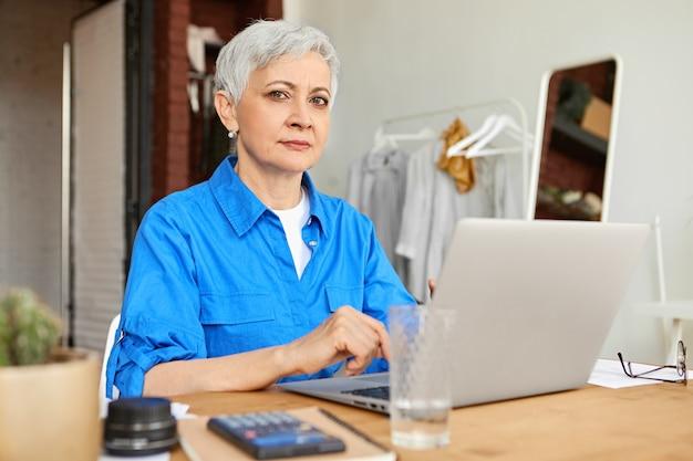 60 년대 스타일리시 그레이 머리 여성 사진 작가가 열린 노트북 컴퓨터 앞에 집에 앉아 사진을 업로드하고있다. 일반 전자 가제트를 사용 하여 인터넷을 서핑하는 성숙한여 인