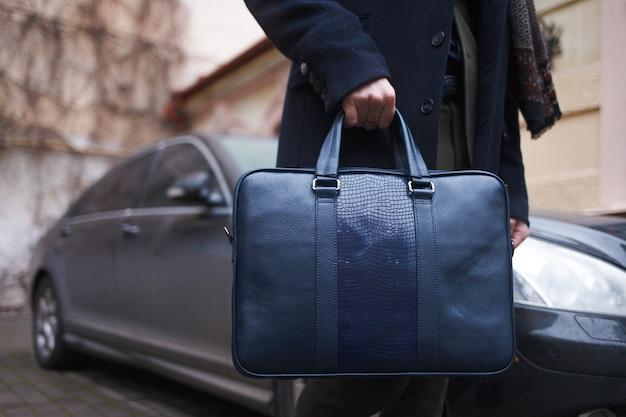 Стильно одетый деловой человек с сумкой в руках стоит на фоне своей машины