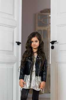 Стильно одетая девушка в кожаной куртке позирует в домашнем интерьере