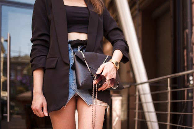 Stylishly dressed young woman holds a handbag and glasses in her hands.