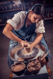 ろくろに粘土の花瓶を成形するスタイリッシュな陶芸家の職人