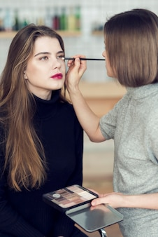 Stylist applying eye makeup on model