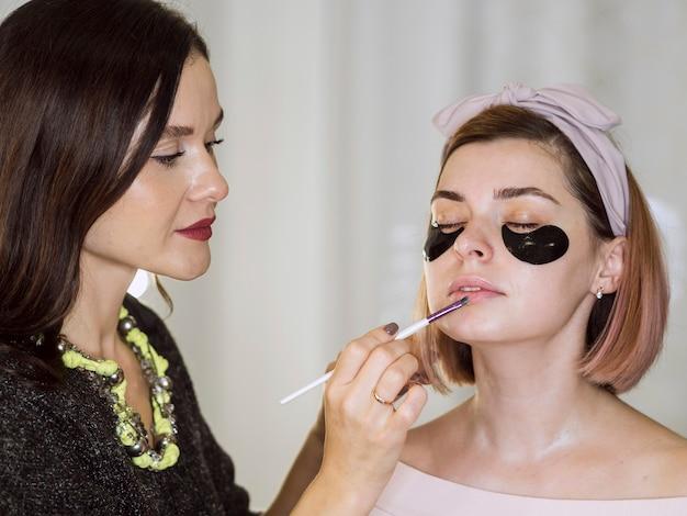 Stylist applying lipstick on natural woman