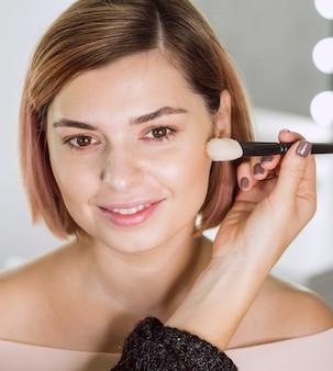 Стилист, наносящий макияж на модель