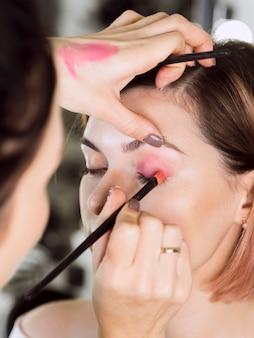 Стилист, применяя розовые тени на модели