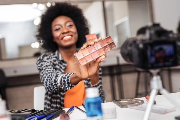 スタイリスト。新しい口紅の色を楽しみながら巻き毛が素晴らしく見える美しい浅黒い肌のモデル