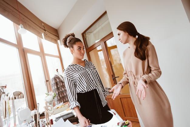 Стилист обсуждает платье с клиентом. две молодые привлекательные женщины, работающие над новым дизайн-проектом. африканская женщина-дизайнер с молодой кавказской женщиной-брюнеткой