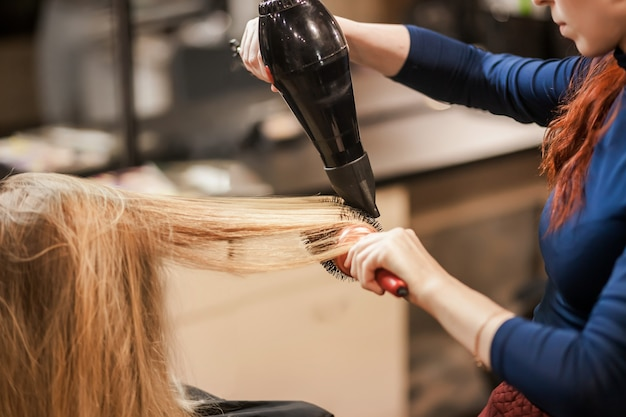 Stylist dries wet hair with hair dryer