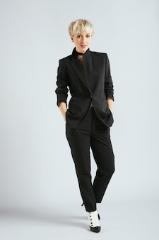 Stylist in elegant black suit , full body. person in sphere of fashion, trendy blonde woman. shopping, indoors
