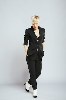 Stylist in elegant black suit, full body. person in sphere of fashion, trendy blonde woman. shopping, indoors