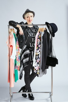 Stylist in fashionable outfit standing behind dresses on rack, full body. person in sphere of fashion choosing clothes, looking at camera. shopping, indoors, buying of clothes