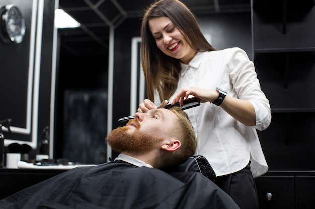 Stylist girl shaves beard man in barbershop