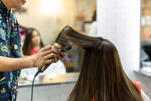 Stylist hairdresser making hairstyle using hair dryer blowing on customer hair