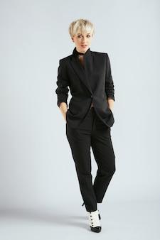 カメラ、全身を見ているエレガントな黒のスーツのスタイリスト。ファッション界の人、流行の金髪女性。ショッピング、屋内