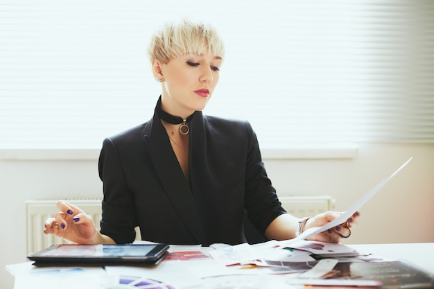 Стилист в элегантном черном костюме сидит за столом и читает, знаток моды. женщина в сфере моды с планшетом. шоппинг, в помещении, по пояс
