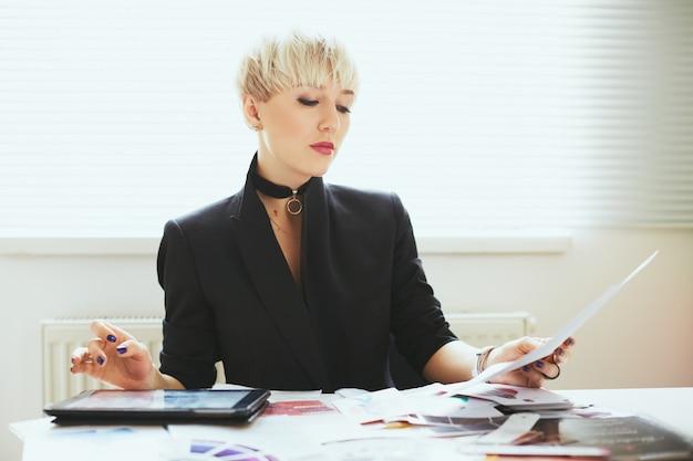 テーブルに座って読書をしているエレガントな黒のスーツを着たスタイリスト、ファッションのエキスパート。タブレットでファッションの領域の女性。ショッピング、屋内、腰を上げる