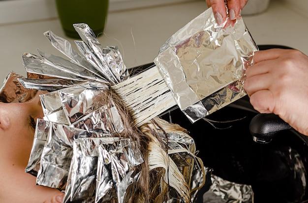 스타일리스트는 모델 머리카락에서 호일을 벗고 있습니다. 표백 또는 염색 공정. 뷰티 살롱, airtouch 기술을 사용한 세련된 헤어 컬러링