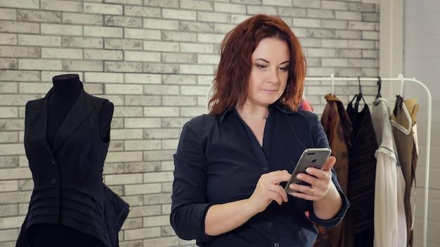 Стилист работает на швейной фабрике, используя мобильный телефон и набирая сообщение. зрелая женщина-модельер с сообщением типов мобильного телефона в ателье пошива одежды и манекенов.
