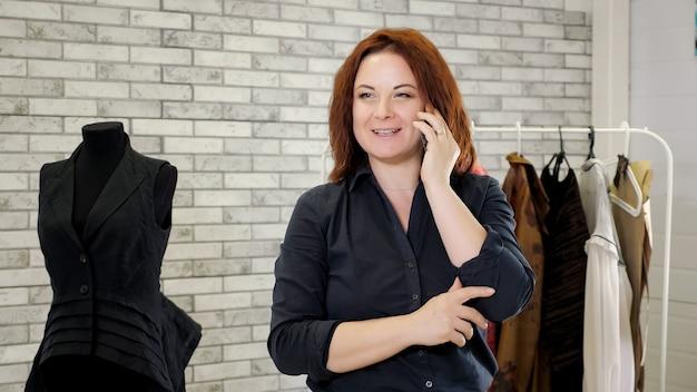 Стилист работает в мастерской швейной фабрики, используя мобильный телефон для работы. портрет зрелого модельера женщины разговаривает с клиентом на смартфоне в ателье одежды. бизнес по производству одежды.