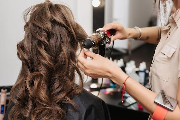 스타일리스트는 전문 미용실에서 긴 갈색 머리를 가진 여성의 곱슬 머리를 만듭니다.