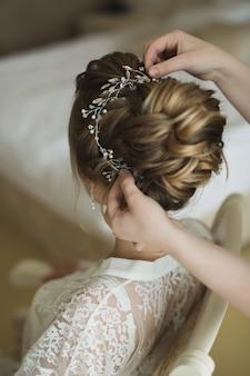 Стилист делает прическу невесте