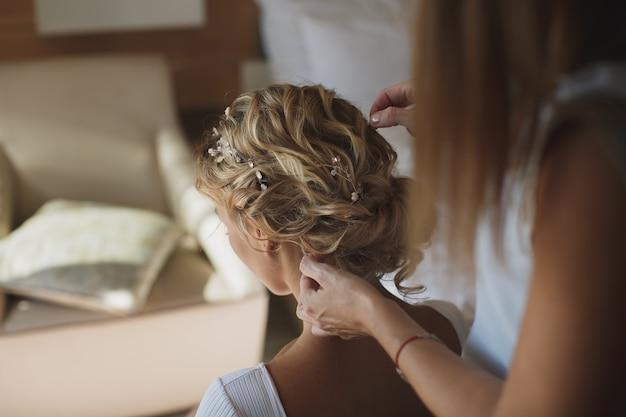 스타일리스트는 머리카락을 신부로 만듭니다.