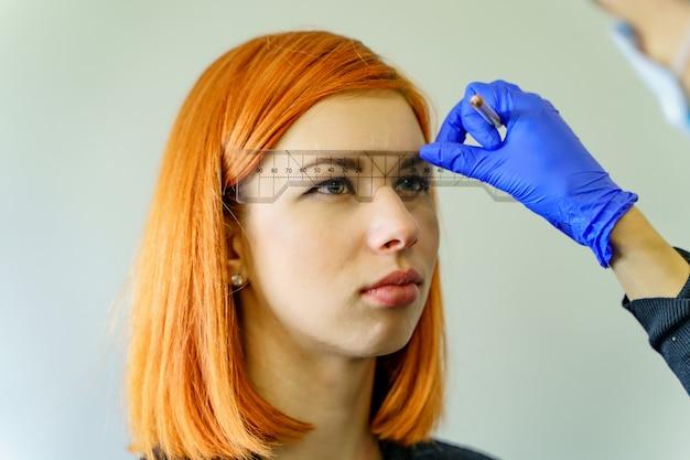 Стилист измеряя брови с линейкой на рыжеволосой женщине. микропигментация, работа в салоне красоты.