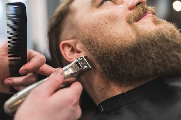 Stylist trimming beard of client