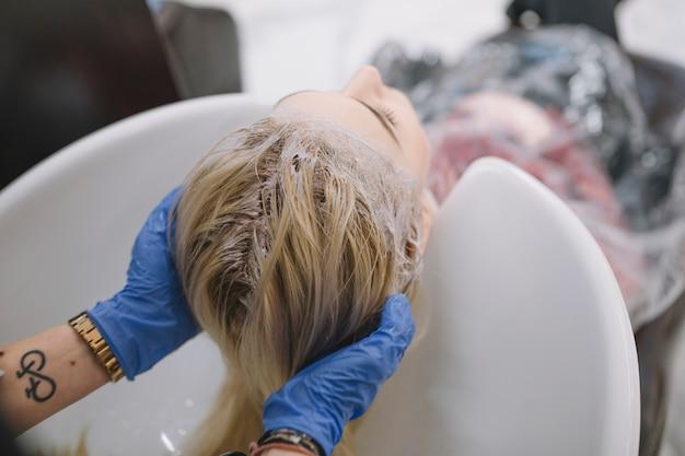 Stylist washing off dye above sink