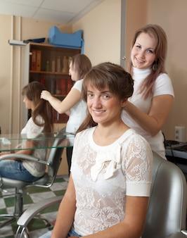 Стилист работает на женских волосах в салоне