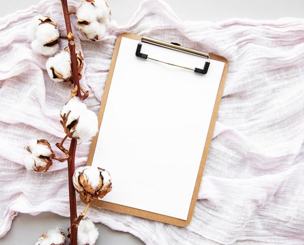 定型化された整理されたオフィスアクセサリークリップボード、綿の花。白い背景の上の女性のファッションアクセサリー。フラットレイトップビュー