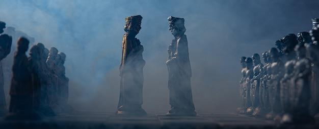 Стилизованные шахматные фигуры на доске с черным фоном, дымом и выборочным фокусом