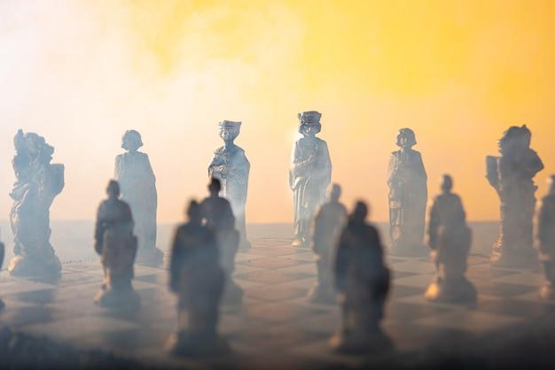 Стилизованные шахматные фигуры на доске с оранжевым фоном, дымом и выборочным фокусом