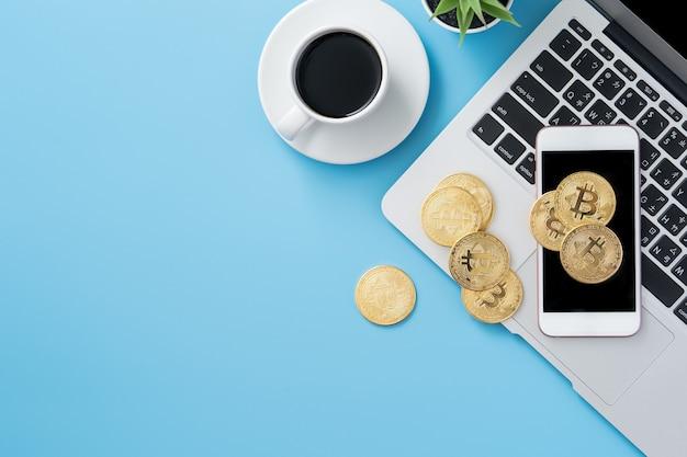 Стилизованный чистый синий офисный рабочий стол с биткойнами, смартфоном, ноутбуком и кофейной чашкой