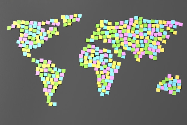 Stylized image of the world map from stickers pasted on the dark wall