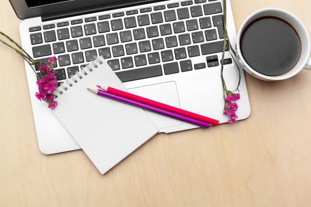 コーヒーカップとラップトップの様式化された女性のオフィスデスク