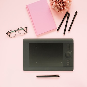 Stylus and graphic digital tablet with stationery on pink background