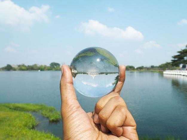 Вручите держать хрустальный шар на общественном парке suan luang rama ix в бангкоке, thailandat.