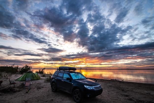 日没の川岸でのキャンプでスバルフォレスター。