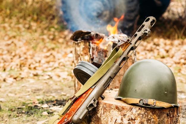 Submachine gun and helmet
