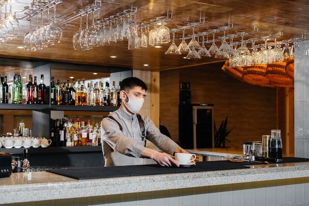 パンデミック時のモダンなカフェでのおいしいオーガニックコーヒーのマスクでのバリスタの提出