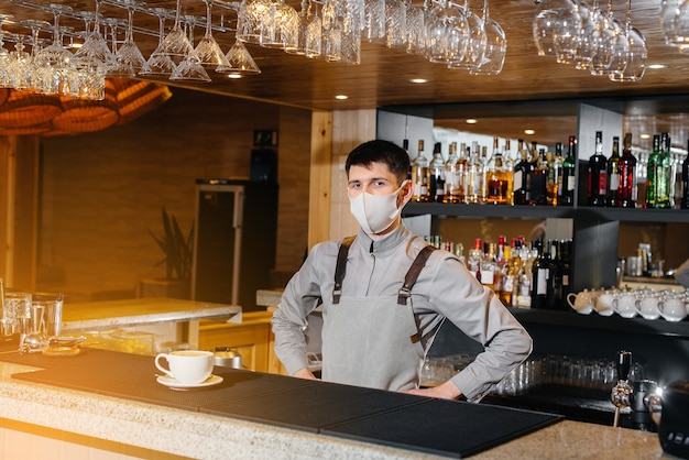 パンデミック時にモダンなカフェで美味しいオーガニックコーヒーのマスクをしたバリスタの提出。