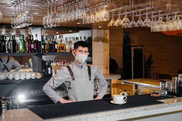 대유행 기간 동안 현대적인 카페에서 맛있는 유기농 커피 마스크에 바리 스타를 제출합니다.