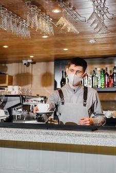 パンデミックの最中にモダンなカフェで美味しいオーガニックコーヒーのマスクをしたバリスタの提出。