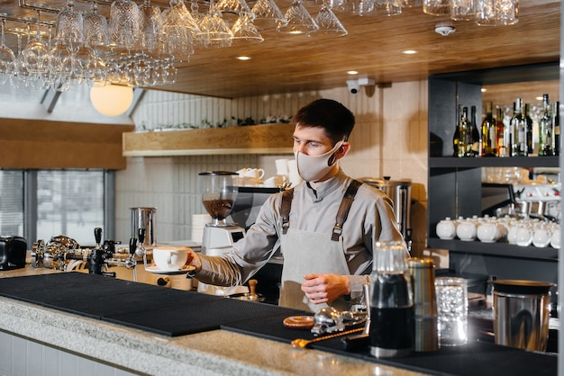 Представление бариста в маске вкусного натурального кофе в современном кафе во время пандемии.